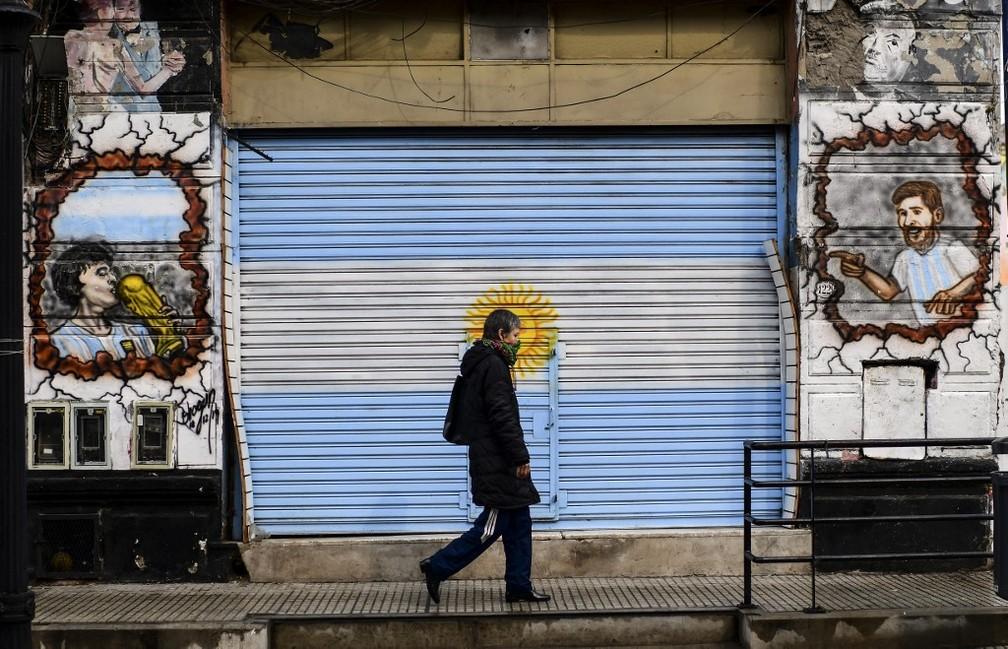 Homem passeia de máscara em frente a estabelecimento de portas fechadas em Buenos Aires, na Argentina, na quarta-feira (26) — Foto: Ronaldo Schemidt/AFP