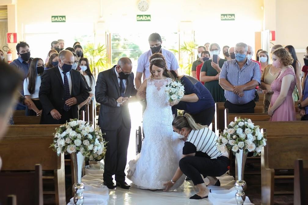 Adarlele de Lara, de 26 anos, levantando-se da cadeira de rodas durante a cerimônia de casamento, em União da Vitória — Foto: Arquivo pessoal