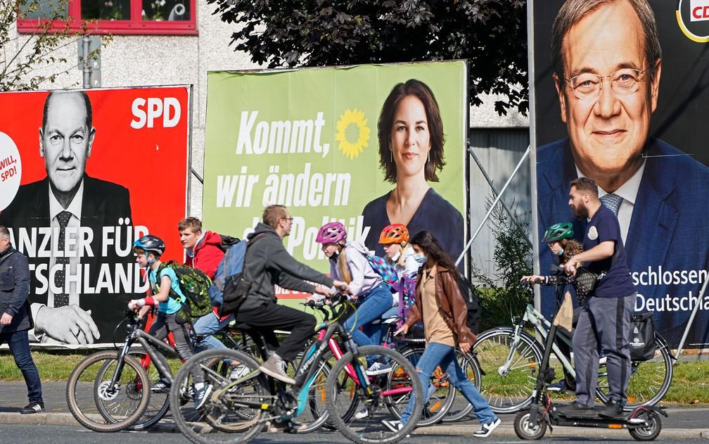 Ciclistas passam em frente a outdoors dos três principais candidatos ao posto de primeiro-ministro alemão: Olaf Scholz, do Partido Social Democrata (SPD), Annalena Baerbock, do Partido Verde, e Armin Laschet, da União Social Democrata (CDU), em foto de 23 de setembro — Foto: AP Photo/Martin Meissner