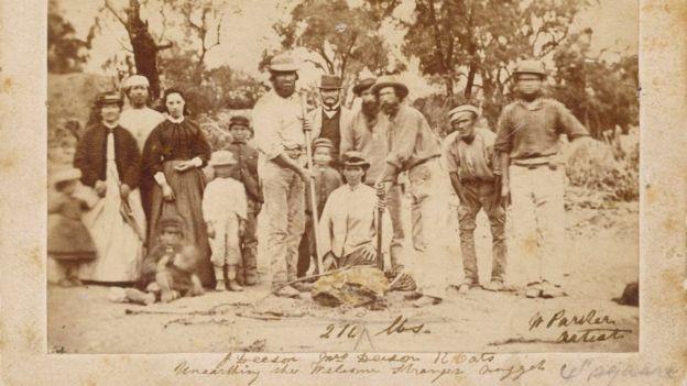 Famílias locais posaram ao lado dos mineradores que descobriram a pepita - que já tinha sido fragmentada antes desta foto (Foto: STATE OF VICTORIA MUSEUM via BBC News Brasil)