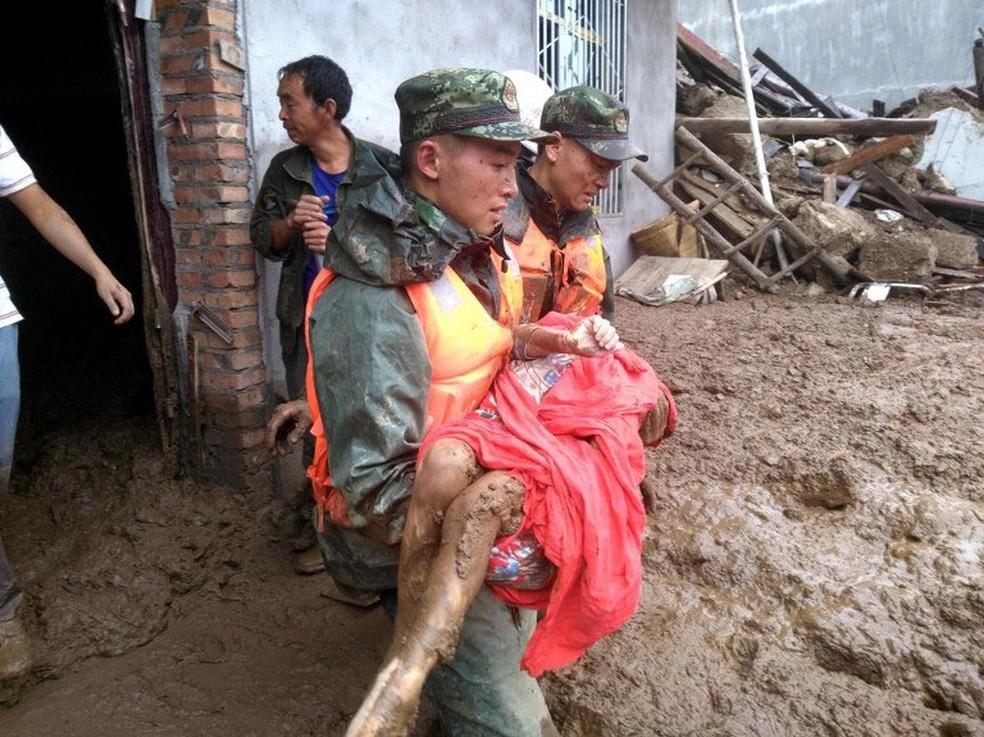 Sobrevivente é resgatada após deslizamento na província de Sichuan, no sudoeste da China, nesta terça-feira (8)  (Foto: AFP)