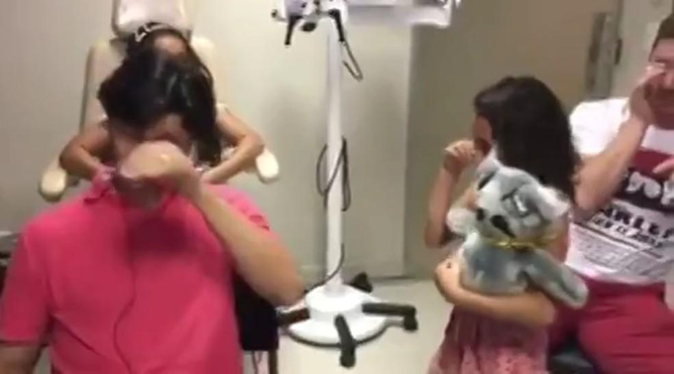 Pai e filha emocionados após teste com implante coclear em Brasília (Foto: Reprodução)