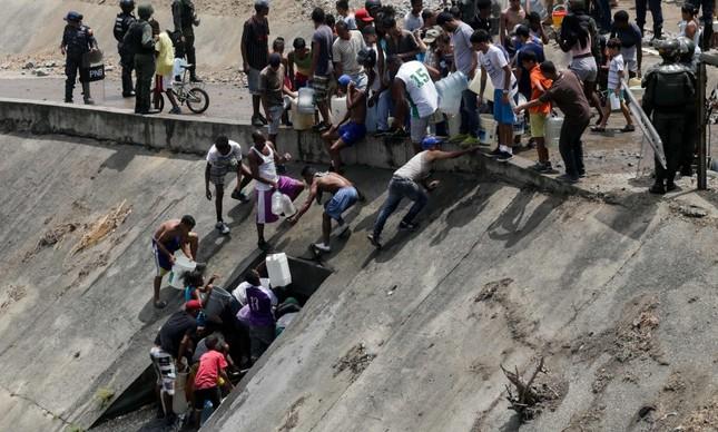 Venezuelanos recolhem água de um cano rompido, ao lado de um canal em Caracas. Sem luz, o abastecimento ficou comprometido