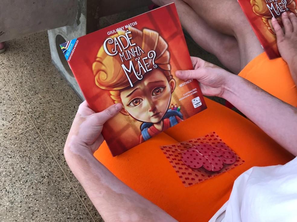 """Detenta da Colmeia, presídio feminino do DF, segura livro """"Cadê minha mãe?"""", da agente penitenciária e escritora Giulieny Matos — Foto: Luiza Garonce/G1"""