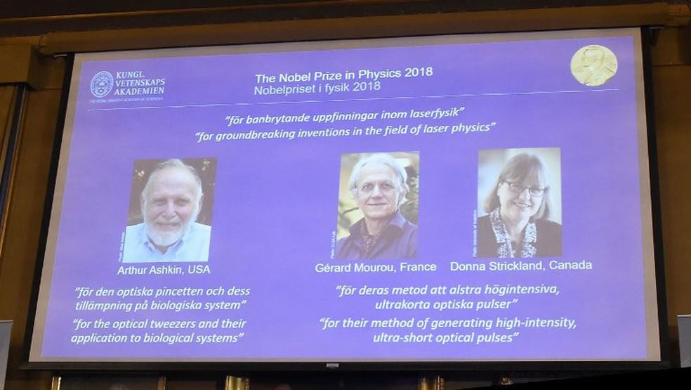 Telão mostrou os nomes dos vencedores do Nobel de Física: Arthur Ashkin (EUA), Gérard Mourou (França) e Donna Strickland (Canadá) — Foto: Hanna Franzen / TT News Agency / AFP
