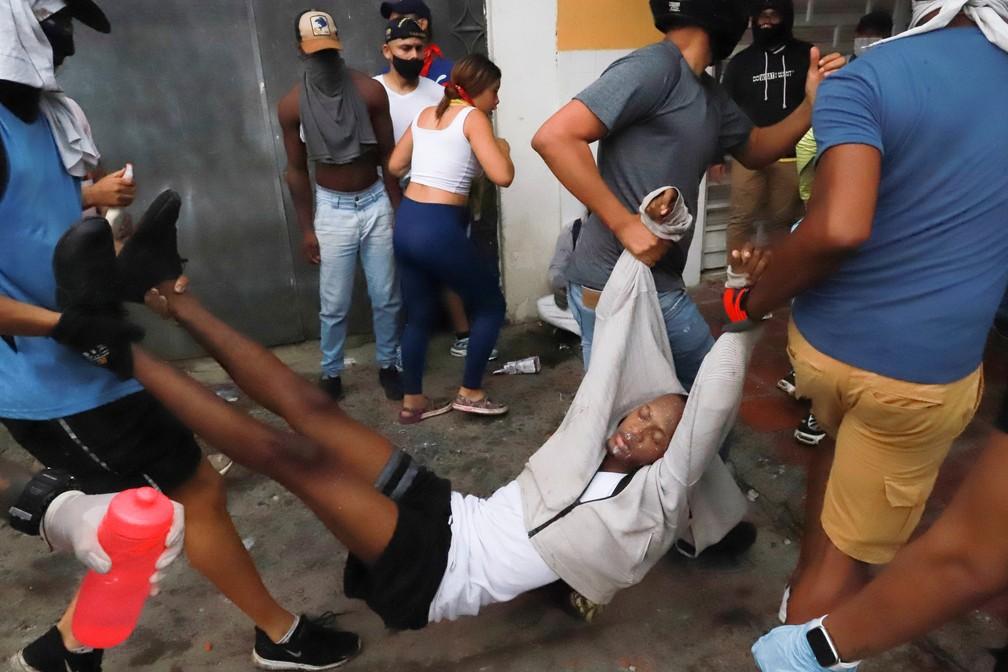 Homem é carregado na cidade de Cali, na Colômbia; manifestantes dizem que ele foi vítima de violência policial durante os protestos no dia 3 de maio de 2021 — Foto: Juan Bautista/Reuters