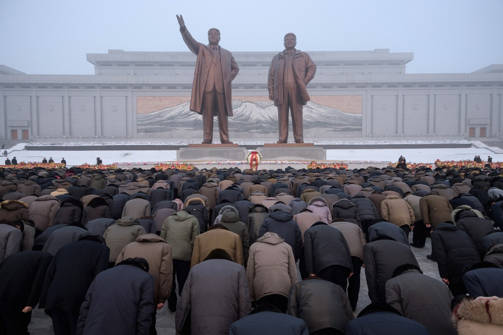 Pessoas se curvam em frente às estátuas dos líderes norte-coreanos mortos Kim Il Sung e Kim Jong Il durante o dia memorial nacional em Pyongyang, na Coreia do Norte — Foto: Kim Won Jin/AFP