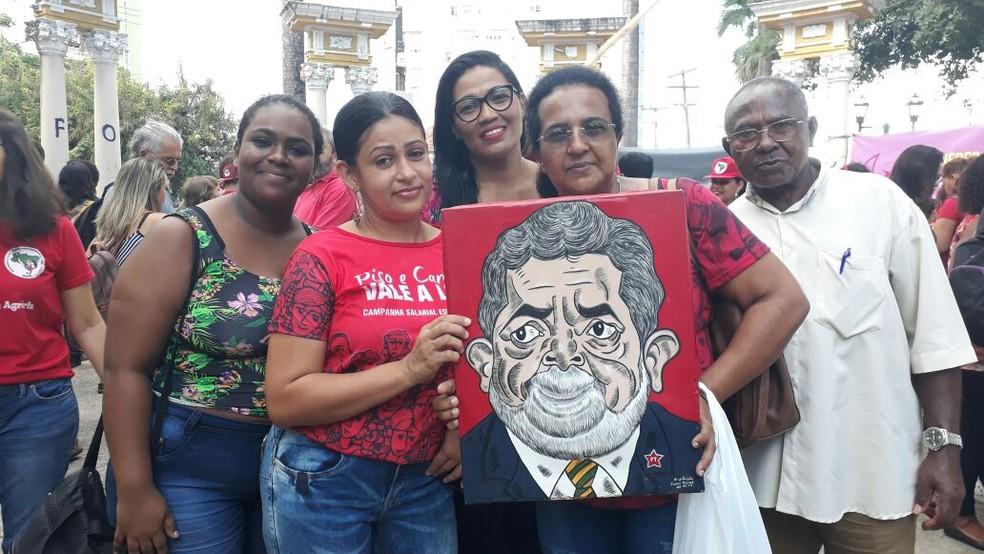 Professora Clícia Roberta de França segura quadro com ilustração de Lula durante o ato (Foto: Marina Meireles/G1)