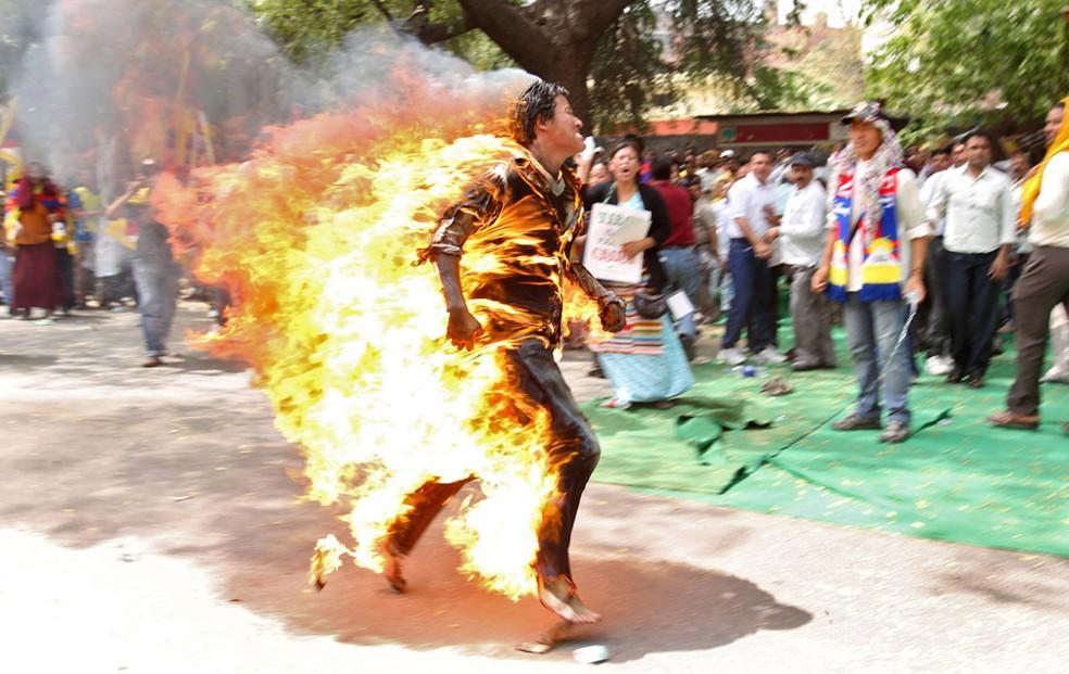 Um exilado do Tibet corre depois de incendiar a si mesmo durante protesto contra a visita do então presidente da China, Hu Jintao, à Índia em 2016. — Foto: Reuters
