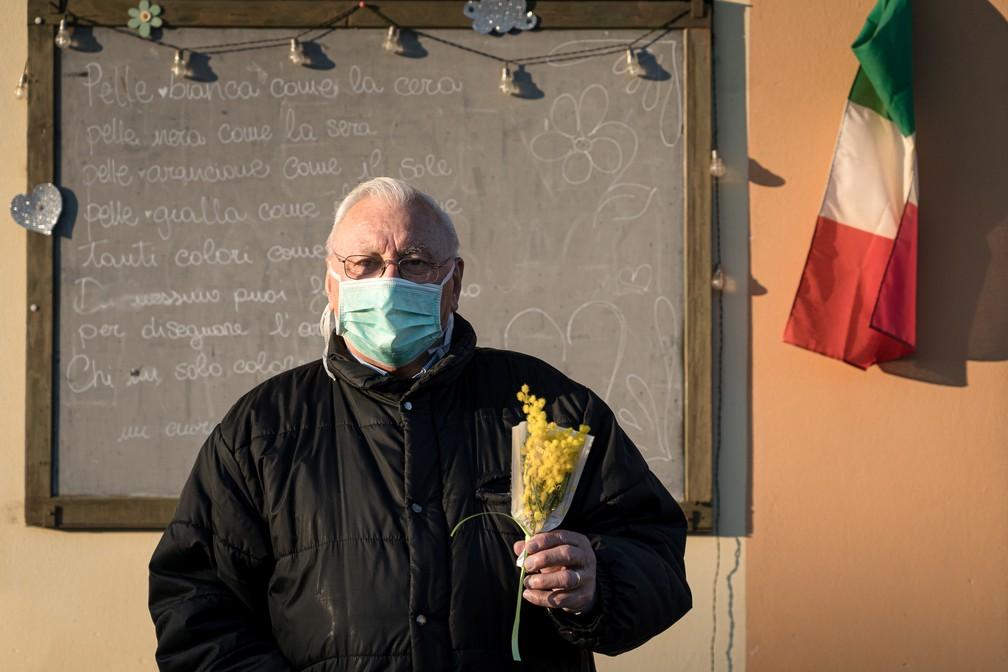 Homem usando máscara protetora contra o Covid-19 em San Fiorano, na Lombardia, segura um buquê de flores. A região, no norte italiano, é a mais afetada pelo novo coronavírus no país.  — Foto: Marzio Toniolo/via Reuters