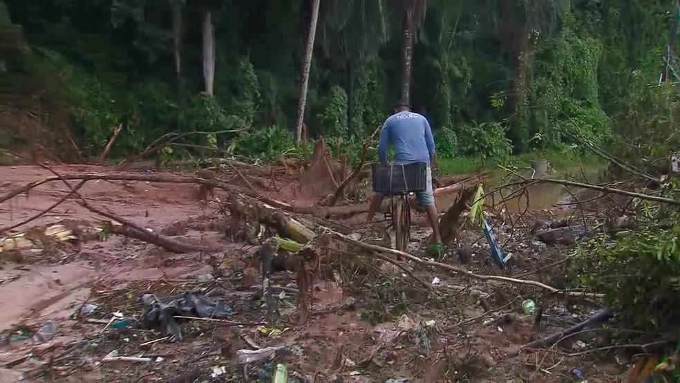 Na Estrada do Passarinho, homem tenta passar com bicicleta por via atingida pelo deslizamento — Foto: Reprodução/TV Globo