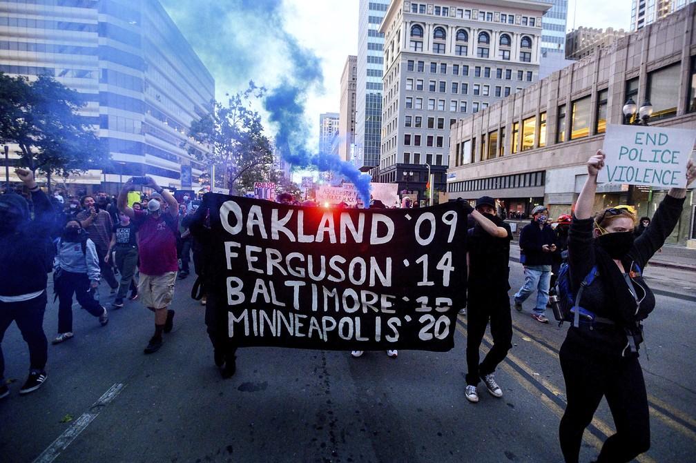 Em Oakland, manifestantes pela morte de George Floyd seguram cartaz com datas e cidades em que homens negros foram mortos por policiais brancos: Oakland, em 2009; Ferguson, em 2014; Baltimore, em 2015; e Minneapolis, 2020. — Foto: Noah Berger/AP