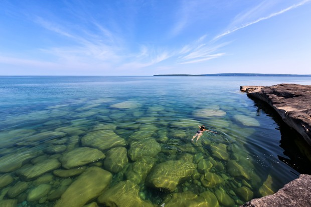 A girl swims in Lake Superior in the upper peninsula of Lake Michigan. Rocks are visable through the glass like, pristine waters. Pictured Rocks National Lakeshore is in the distance. (Foto: Getty Images/iStockphoto)