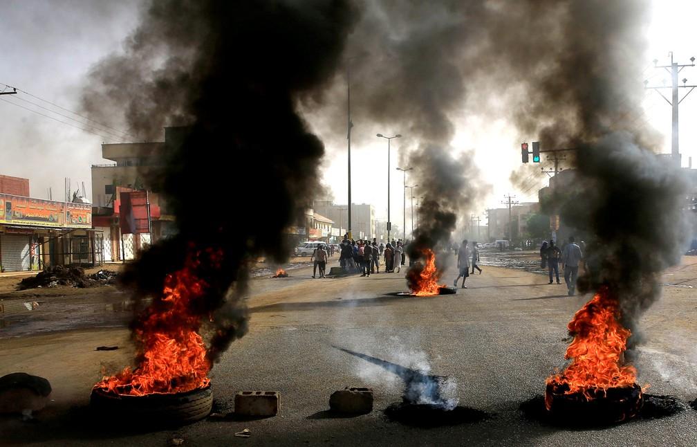 Manifestantes sudaneses utilizam pneus em chamas para erguer uma barricada durante protesto em Cartum, no Sudão, onde exigem que o Conselho de Transição Militar do país entregue o poder a civis — Foto: Reuters