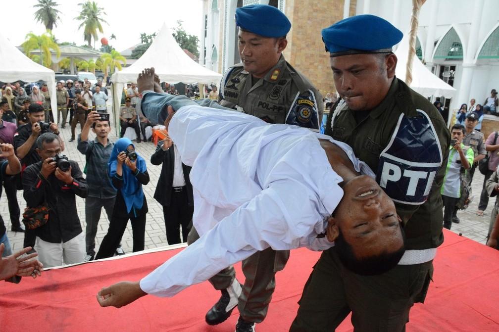 Homem desmaia ao ser açoitado em Aceh Timur, nesta quinta (5)  — Foto: Cek Mad / AFP
