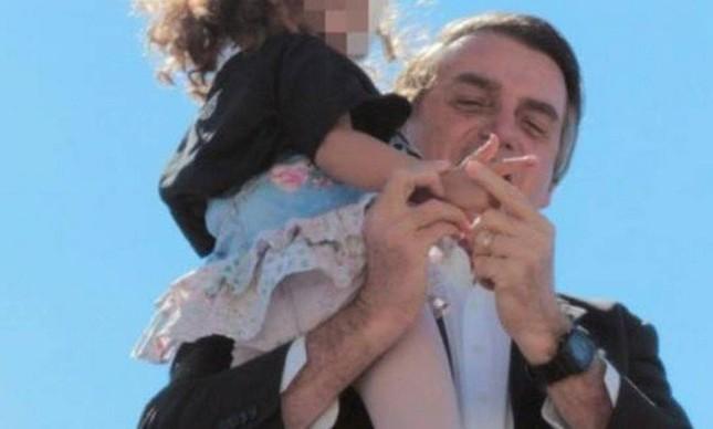 Bolsonaro ensina menina a fazer gesto de tiro na campanha de 2018