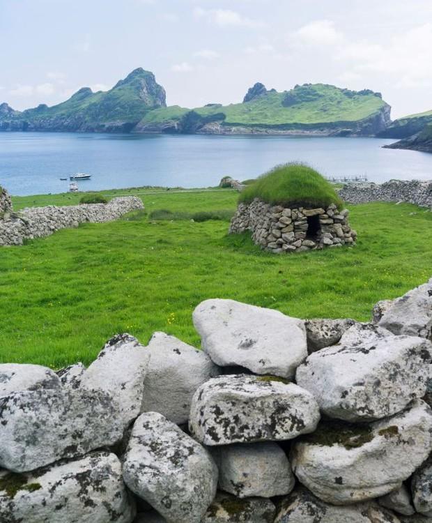 O campo e as construções de pedra formam a paisagem em Hirta (Foto: Getty Images/ Reprodução)