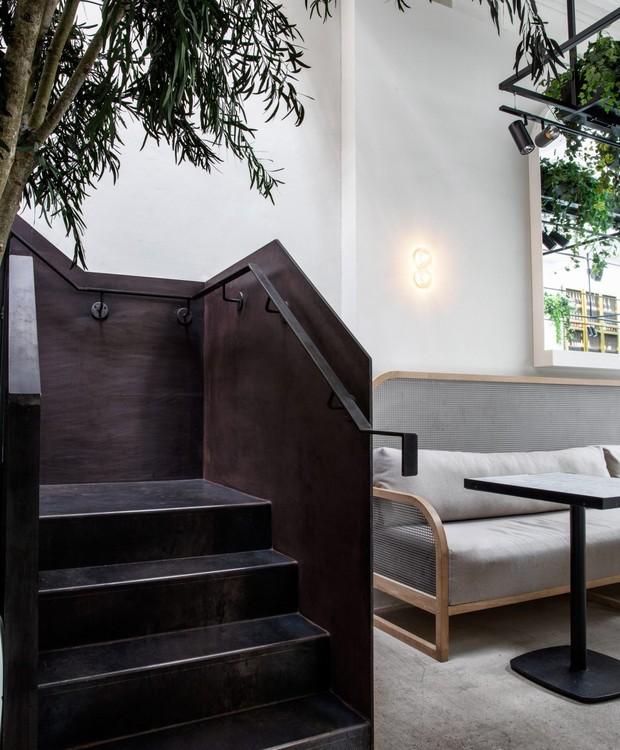 A escada de aço é um ponto escuro na arquitetura. Ela já estava presente no antigo correio e recebeu reforma junto ao novo café (Foto: Dezeen/ Reprodução)