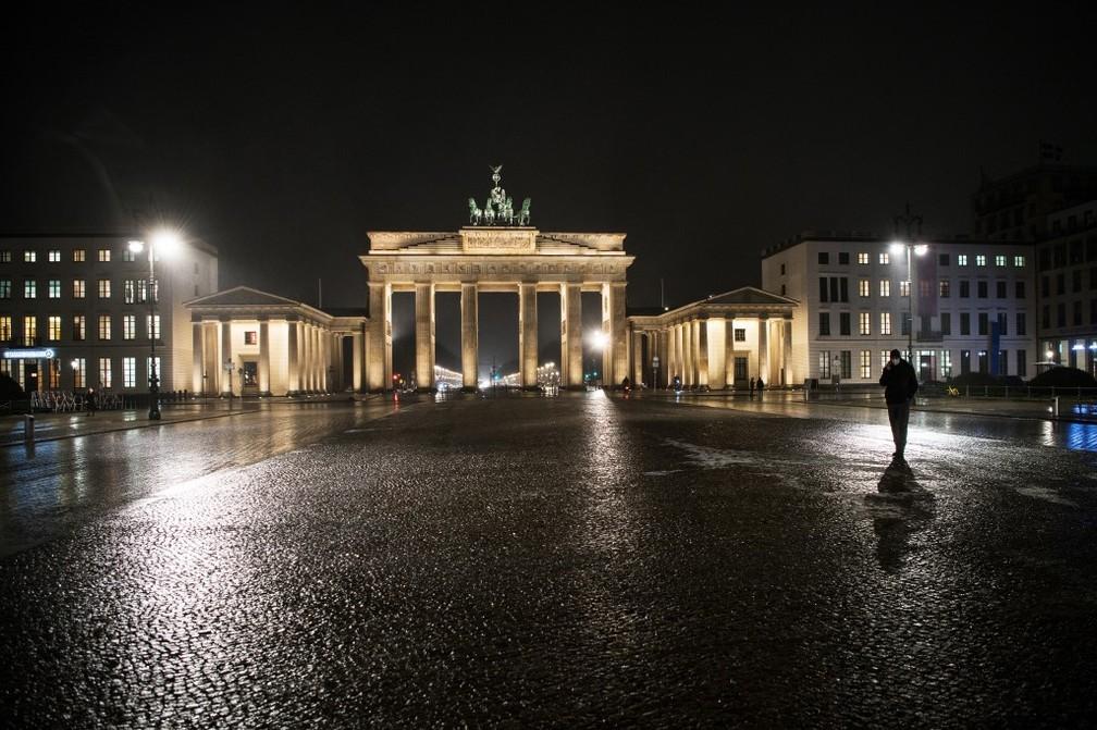 Pessoa anda sozinha em frente ao Portão de Brandemburgo, em Berlim, em ruas vazias por causa das restrições contra a Covid-19, no dia 19 de janeiro. — Foto: Stefanie Loos/AFP