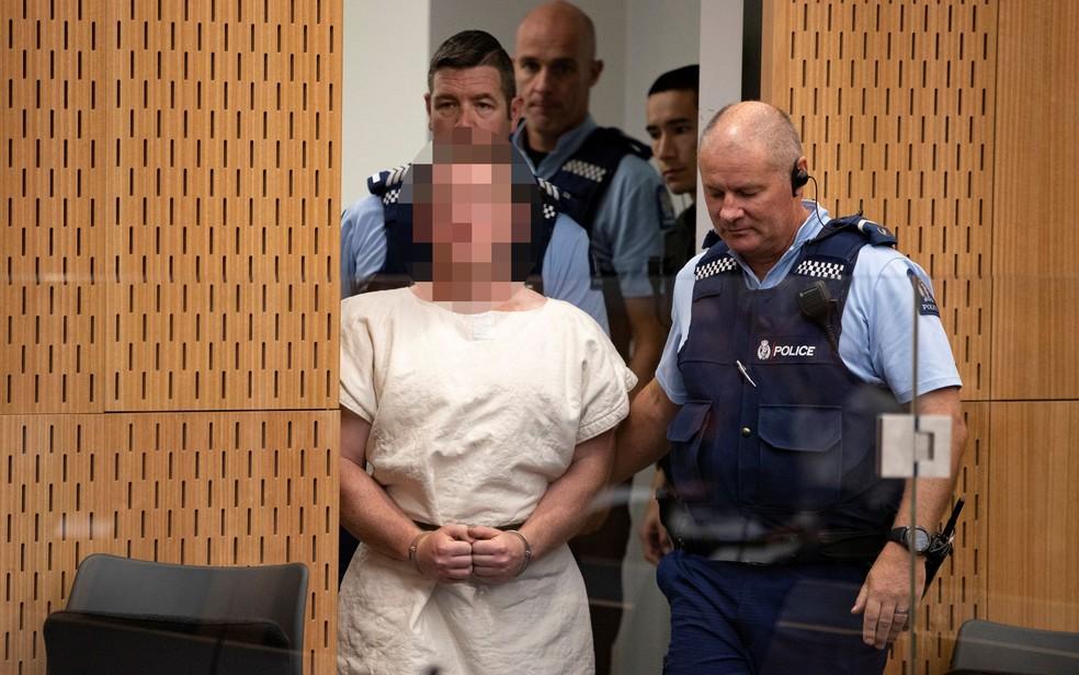 Assassino de ataque a mesquistas é acompanhado por policiais durante sua apresentação à corte do Distrito de Christchurch, na Nova Zelândia, no sábado (16) — Foto: Mark Mitchell/New Zealand Herald/Pool