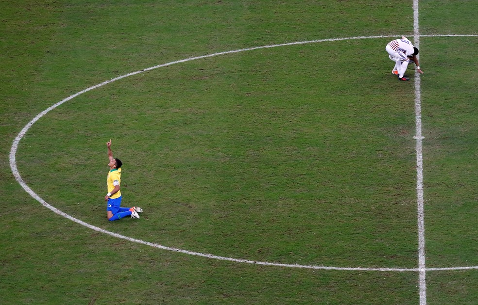 Ajoelhado, o zagueiro agradece após a vitória — Foto: Diego Vara/Reuters
