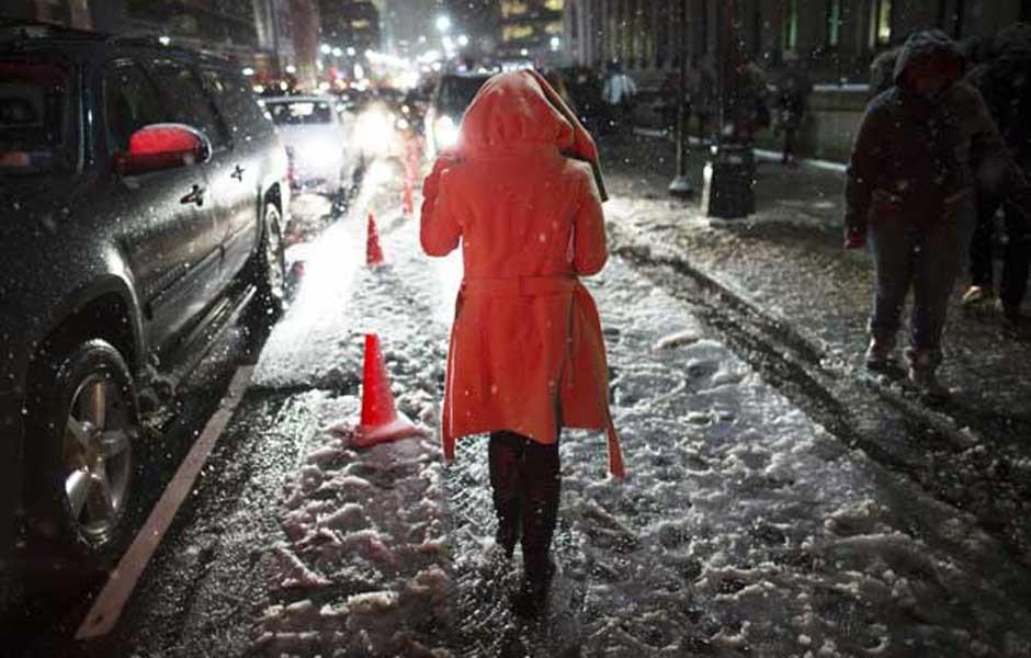 Mulher caminha na neve em rua de Nova York. (Foto: John Minchillo / AP Photo)
