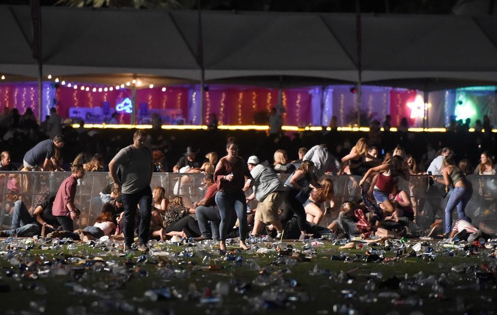 Pessoas correm do local do festival de música country após tiros serem disparados em Las Vegas, nos EUA.  (Foto: David Becker/Getty Images/AFP)