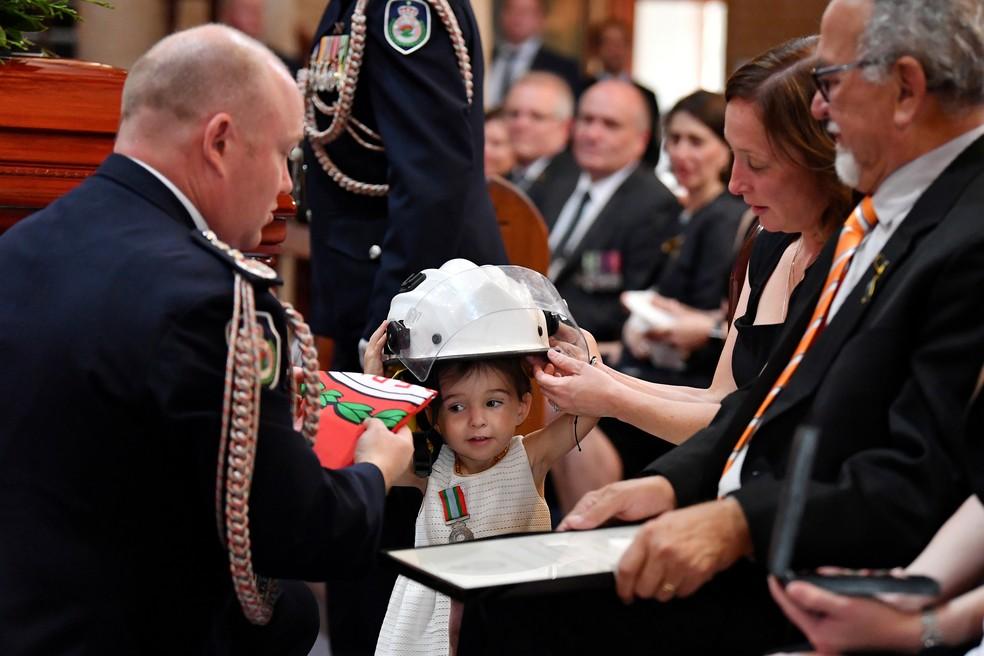 Charlotte O'Dwyer, filha do bombeiro Andrew O'Dwyer, recebe o capacete de seu pai durante velório. — Foto: AAP Image/Dean Lewins/Pool/Reuters