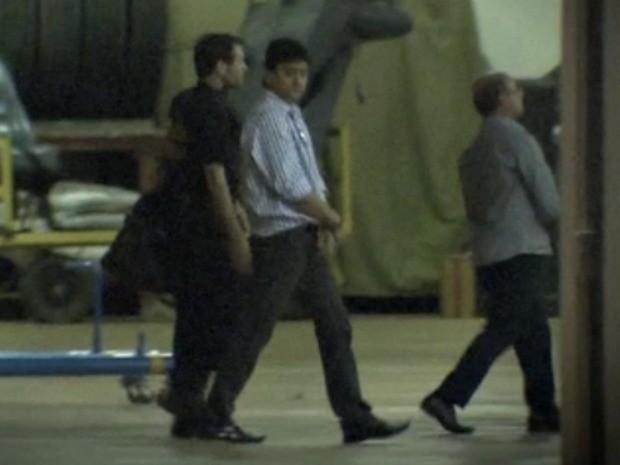 O ex-secretário Eder Moraes e o deputado estadual José Riva algemados pela PF após desembarque em Brasília. (Foto: Reprodução / TVCA)