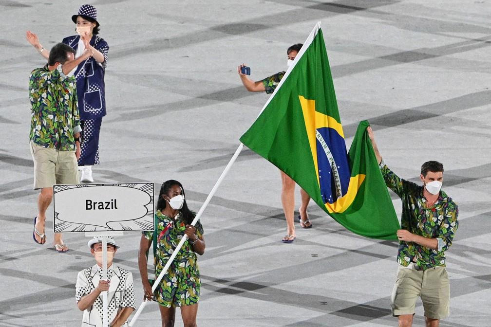 Ketleyn Quadros e Bruno Mossa carregam a bandeira do Brasil durante a cerimônia de abertura dos Jogos Olímpicos de Tóquio, no Japão — Foto: Martin Bureau/AFP