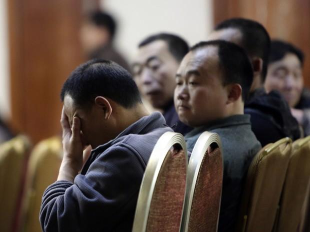 Parentes dos passageiros do avião da Malaysia Airlines participam de reunião com representantes da companhia em Pequim, neste sábado (Foto: Reuters)
