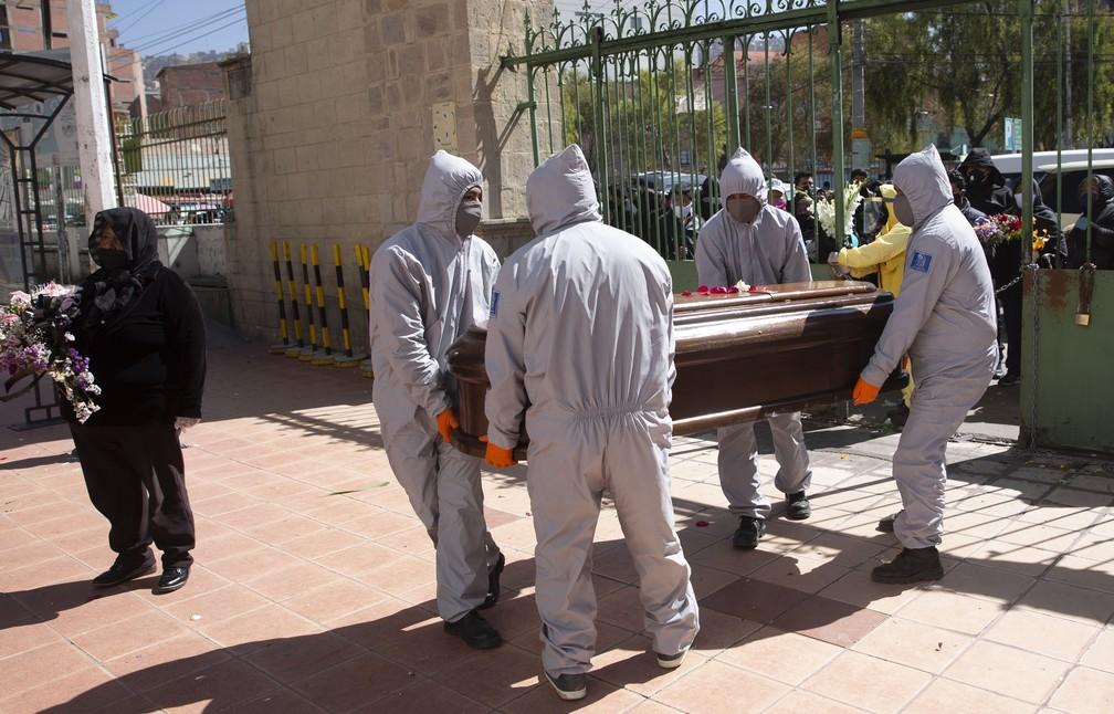 Funcionários de funerária usam roupa de prevenção ao novo coronavírus ao enterrar homem em La Paz, capital da Bolívia, nesta terça (21). Embora corpo não seja de vítima da doença, explosão de casos no país obrigam profissionais a tomarem medidas de precaução — Foto: Juan Karita/AP Photo