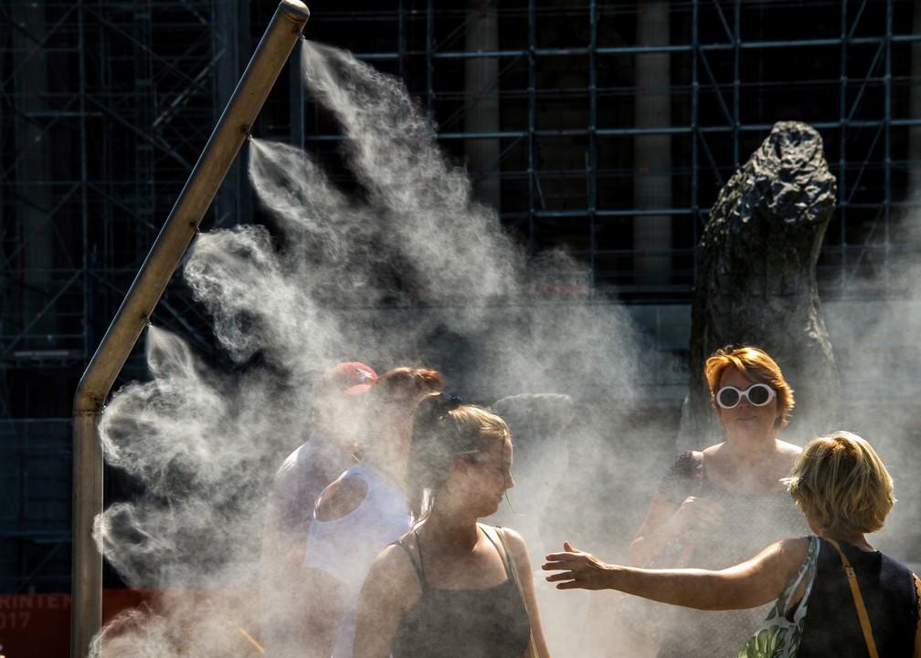 Mulheres se refrescam com borrifador de água público em Lille, na França, durante onda de calor na Europa — Foto: Philippe Huguen/AFP