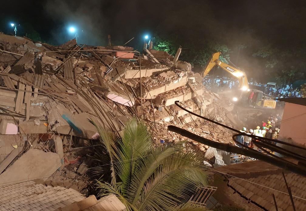 Escavadeiras tentam remover entulho em busca de sobreviventes de desabamento na Índia desta segunda-feira (24) — Foto: Stringer/Reuters