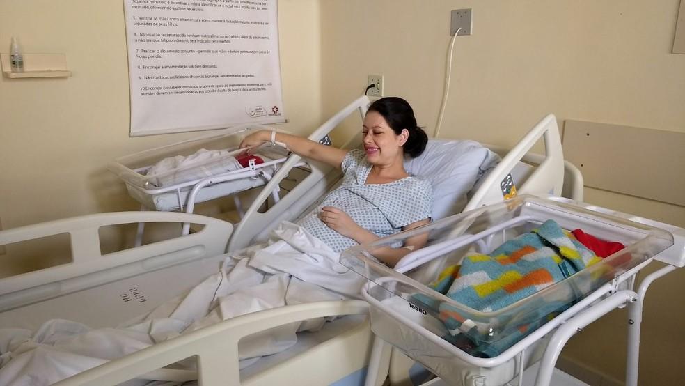 Michele Ferreira Maciel Ribeiro, de 28 anos, entre os filhos gêmeos nascidos em anos diferentes. (Foto: Marcelo Rocha/RPC)