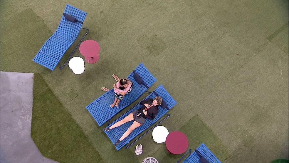 Paula e Hariany conversam no jardim enquanto Tereza fica pensativa no balanço — Foto: TV Globo