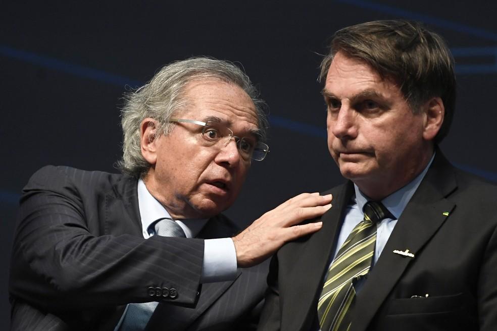 O ministro da economia Paulo Guedes e o presidente Jair Bolsonaro durante cerimônia no Rio de Janeiro, em outubro de 2019 — Foto: Mauro Pimentel/AFP
