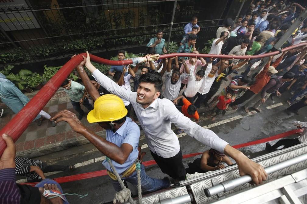 Moradores ajudam os bombeiros a apagar um incêndio em prédio comercial em Daca, Bangladesh, nesta quinta-feira (28)  — Foto: Mahmud Hossain Opu/AP