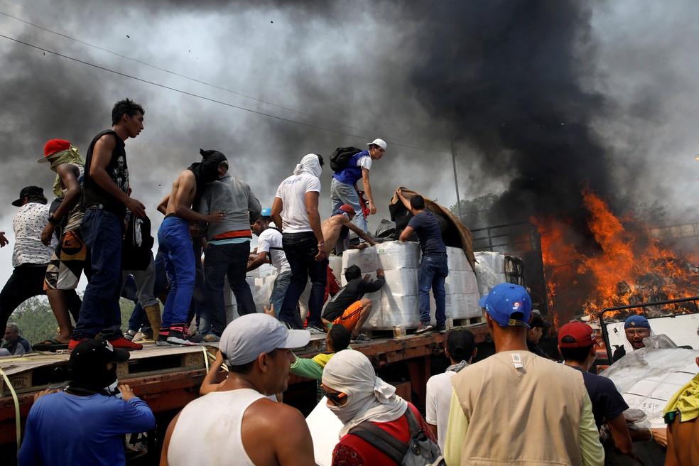Após confrontos com as forças de segurança da Venezuela, manifestantes tentam recuperar a carga do caminhão incendiado — Foto: Marco Bello/Reuters
