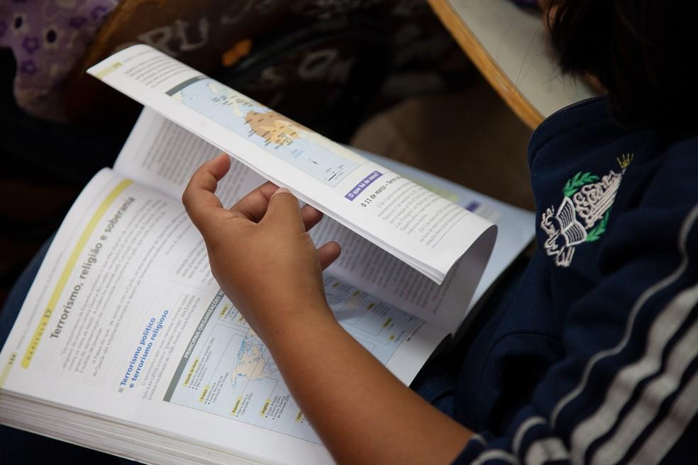 Jovem folheia livro de ensino médio — Foto: Edson Fogaça/Unesco