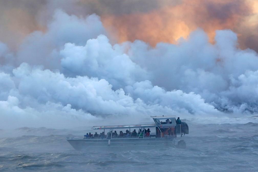 Turistas observam fumaça saindo do mar devido ao contato da lava do vulcão Kilauea na região de Kapoho, a leste de Pahoa, no Havaí (Foto: Terray Sylvester/Reuters)