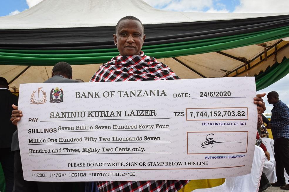 Garimpeiro Saniniu Laizer exibe cópia de cheque que recebeu pela venda de duas tanzanitas na quarta-feira (24) — Foto: Filbert Rweyemamu / AFP