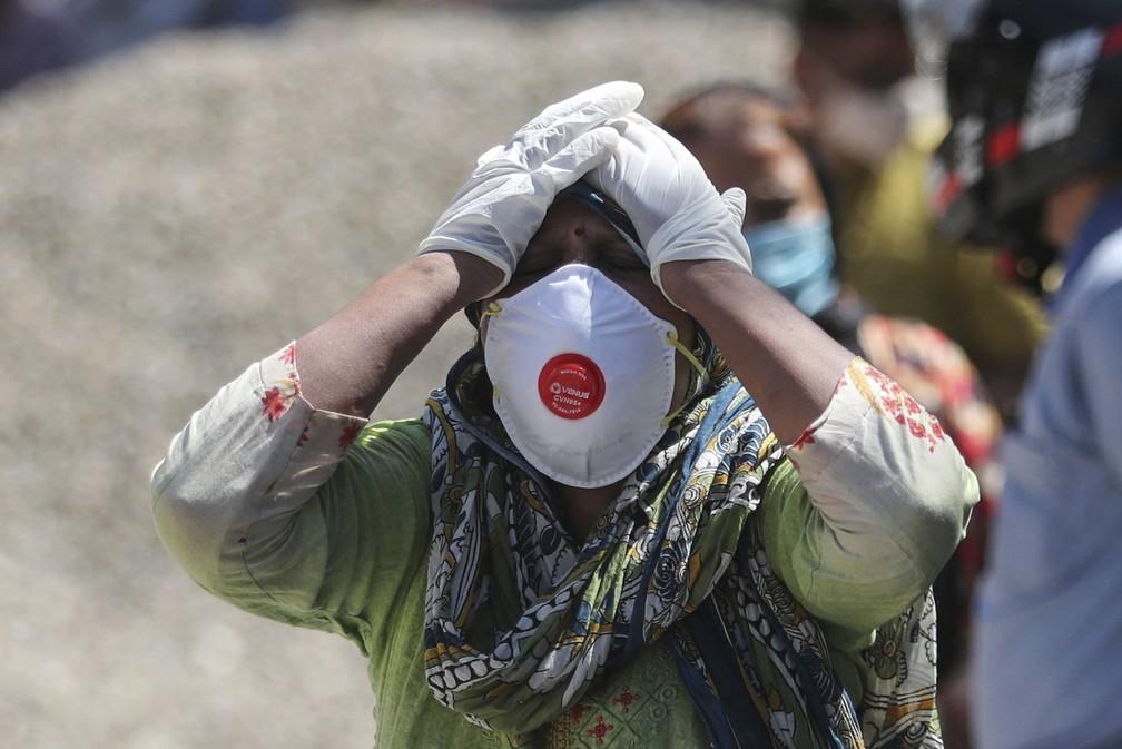 Parente de vítima da Covid-19 coloca as mãos na cabeça em um crematório em Jammu, na Índia, em 25 de abril de 2021 — Foto: Channi Anand/AP
