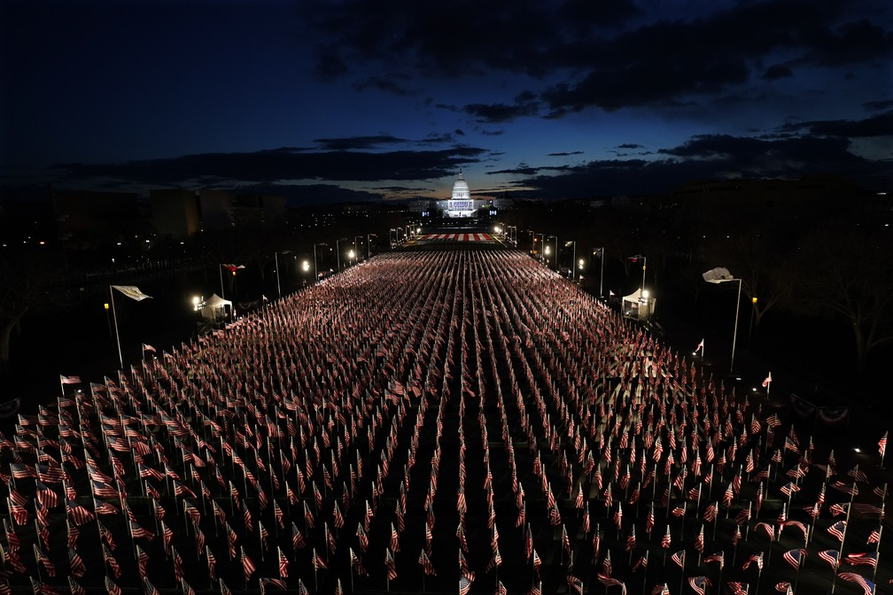 Bandeiras alinham-se no National Mall em direção ao Capitólio dos EUA, em Washington, enquanto durante o amanhecer no dia da cerimônia de posse do presidente eleito Joe Biden, nesta quarta-feira (20)    — Foto: Julio Cortez/AP