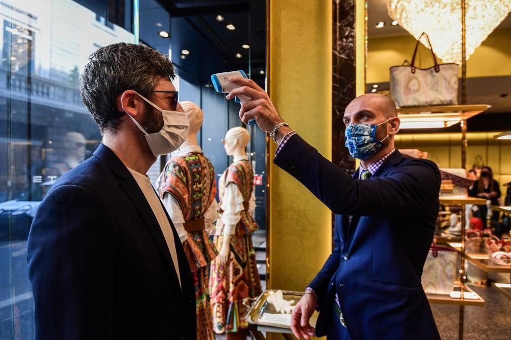 18 de maio - Um cliente tem a temperatura corporal medida ao entrar em uma loja em Milão, na Itália, durante a reabertura do comércio no país após dois meses de bloqueio para conter a propagação da COVID-19 — Foto: Miguel Medina/AFP