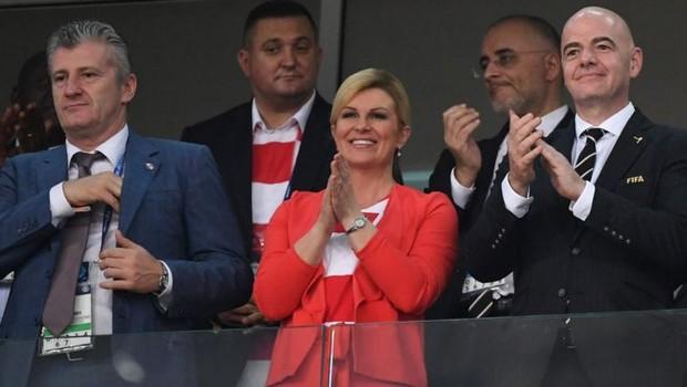 A presidente da Croácia, Kolinda Grabar-Kitarovic, assistiu a vários jogos da seleção na Rússia; em um deles, ficou ao lado de Davor Suker (à esq.), estrela do time na Copa de 98 (Foto: AFP via BBC)