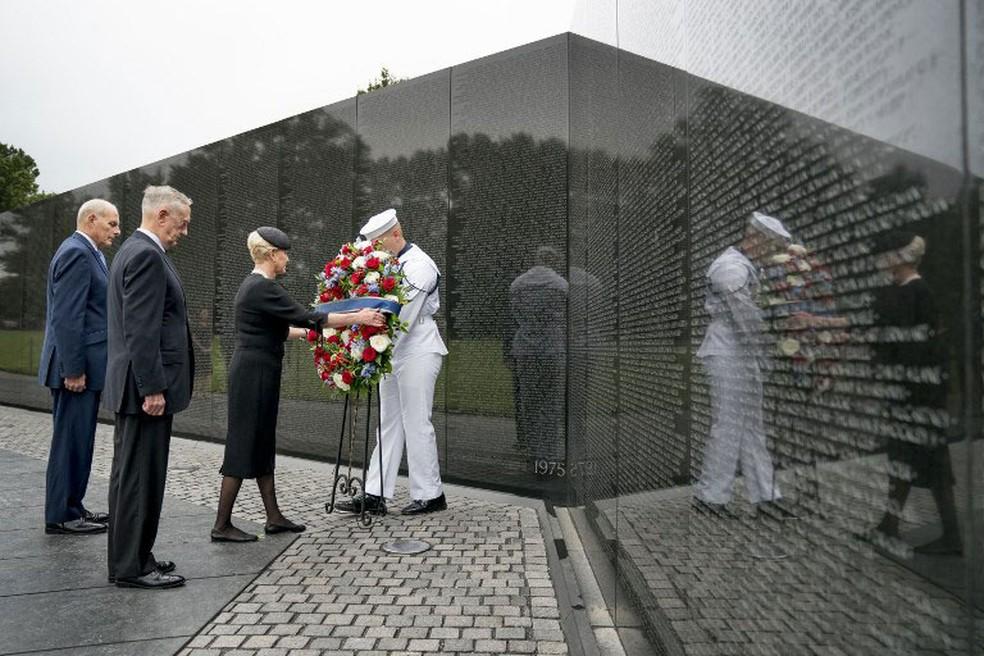 Cindy McCain, viúva do senador John McCain, acompanhada do chefe de gabinete da Casa Branca, John Kelly, e do secretário de Defesa, Jim Mattis, deixa coroa de flores no Memorial dos Veteranos do Vietnã, na manhã deste sábado (1º) (Foto:  Andrew Harnik / AFP)