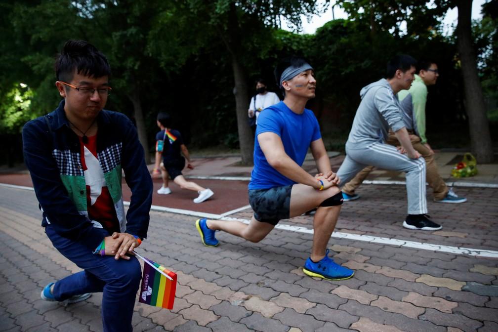 Participantes se aquecem para uma corrida de 5,17 km para marcar o Dia Internacional contra Homofobia, Transfobia e Bifobia, em Pequim, na China (Foto: Thomas Peter/Reuters)