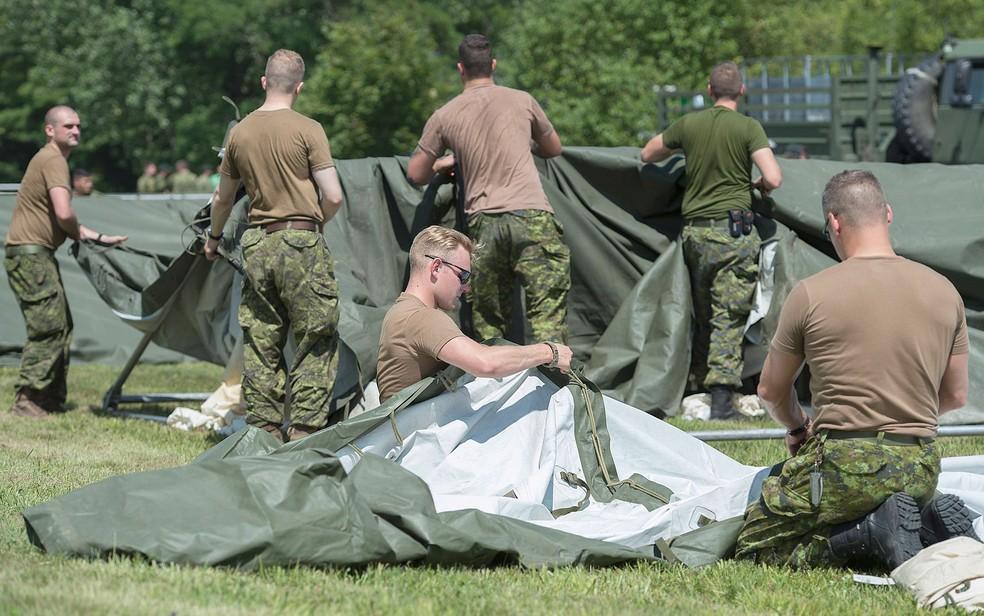 Membros das Forças Armadas do Canadá montam tendas para solicitantes de asilo na fronteira entre o Canadá e os EUA em Lacolle, Quebec, na quarta (9) (Foto: Graham Hughes/The Canadian Press via AP)