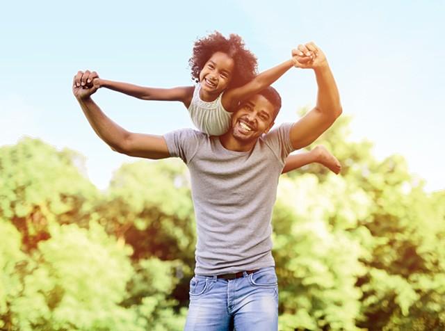 Pai e filha negros se divertem sorrindo e brincando de carregar a criança no ombro fazendo aviãozinho (Foto: Thinkstock)